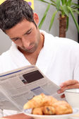 Man reading a journal over breakfast — Stock Photo