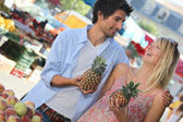Young couple holding pineapples at a market stall — Stock Photo