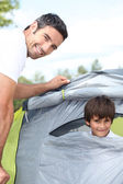 A 35 years old man and a little boy inside a canvas tent — Stock Photo