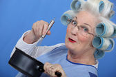 Cheeky older woman in rollers whisking sauce — Stock Photo