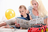 Woman reading a book to her son — Stock Photo
