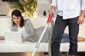 Vysávání muž a žena, pracující na svém laptopu — Stock fotografie