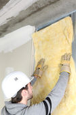Man attaching insulation to wall — Stock Photo