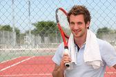 Un giocatore di tennis in posa davanti a una corte di tennis con la sua racchetta. — Foto Stock