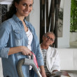 A young woman vacuuming at a senior woman's home — Stock Photo