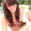 Teenage girl applying suncream at the beach — Stock Photo