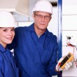Stock Photo: Electriciand his female colleague checking electrical outlet
