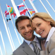 Businessman and woman with flags. - Zdjęcie stockowe