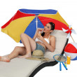 Brunette laying on lounger drinking cocktail - Stock Photo