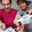Couple playing a games console — Stock Photo #8421789