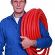 Fully-fledged plumber carrying red hose - Stock Photo