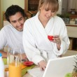 Couple having breakfast in front of laptop - Stock Photo