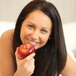Naked woman eating an apple in bed — Stock Photo #8422437