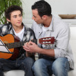 Stock Photo: Father and teenage son playing guitar