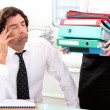 Office worker overwhelmed by load of work — Zdjęcie stockowe #8422580