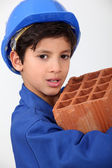 Little boy carrying brick — Stock Photo