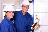 An electrician and his female colleague checking an electrical outlet — Stock Photo