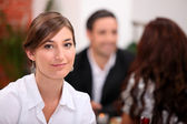 Focus on a woman sitting in a restaurant with other diners in the backgroun — Stock Photo