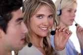 Three employees holding headsets — Stock Photo