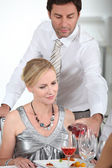 A man serving wine to a woman at the start of a posh dinner. — Stock Photo