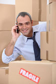 A 40-45 years old employee calling someone in a room full of cardboard boxe — Stock Photo