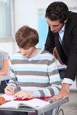 Teacher checking pupils work — Stock Photo