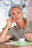 A 65 years old man looking dynamic is calling — Stock Photo