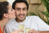 Couple sat in front of packed boxes drinking champagne — Stock Photo