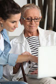Elderly woman using laptop with carer — Stock Photo
