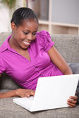 Black woman with sofa on couch — Stock Photo
