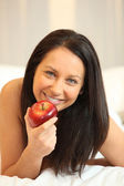 Naked woman eating an apple in bed — Stock Photo