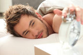 Man in bed turning off alarm — Stock Photo