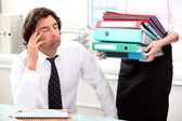 Office worker overwhelmed by load of work — Stock Photo
