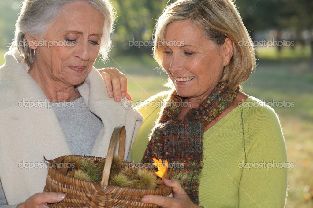 A mid age blonde woman and an older woman holding a wickerwork basket full of chestnuts — Stock Photo #8421107