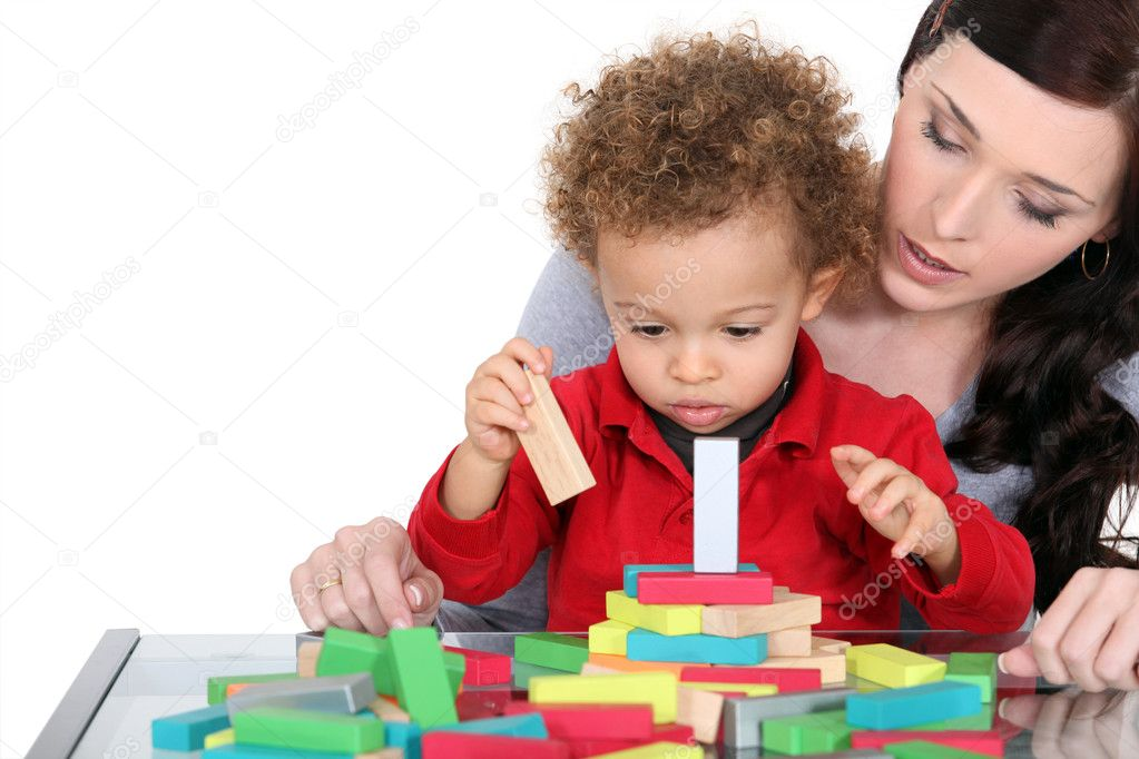 Woman and child playing with wooden blocks — Stock Photo #8421986