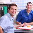 Two male colleagues sat in an office smiling and watching the camera - Stock Photo