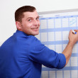 An employee dressed in blue jumpsuite is writing on a calendar — Stock Photo