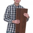 A male carpenter holding a couple of planks. — Stock Photo