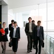 Foto Stock: Businesspeople walking in hallway