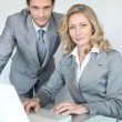 A businessman and a businesswoman working in front of a laptop and looking — Stock Photo #8455192