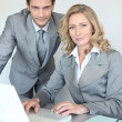 Stock Photo: A businessman and a businesswoman working in front of a laptop and looking