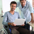 Man in wheelchair holding laptop — Stock Photo