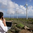 Stock Photo: Young businessmon phone next to wind turbines