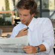 Young man relaxing reading newspaper — Stock Photo