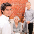 Young man looking over his shoulder as a senior couple make to leave a rest — Stock Photo