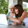 Stock Photo: Elderly woman and girl with computer