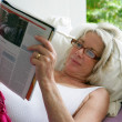 Elderly woman reading a magazine — Stock Photo
