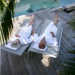 Foto Stock: Couple lounging by pool