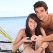 Stock Photo: Young couple steering catamaran