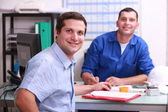 Two male colleagues sat in an office smiling and watching the camera — Foto Stock